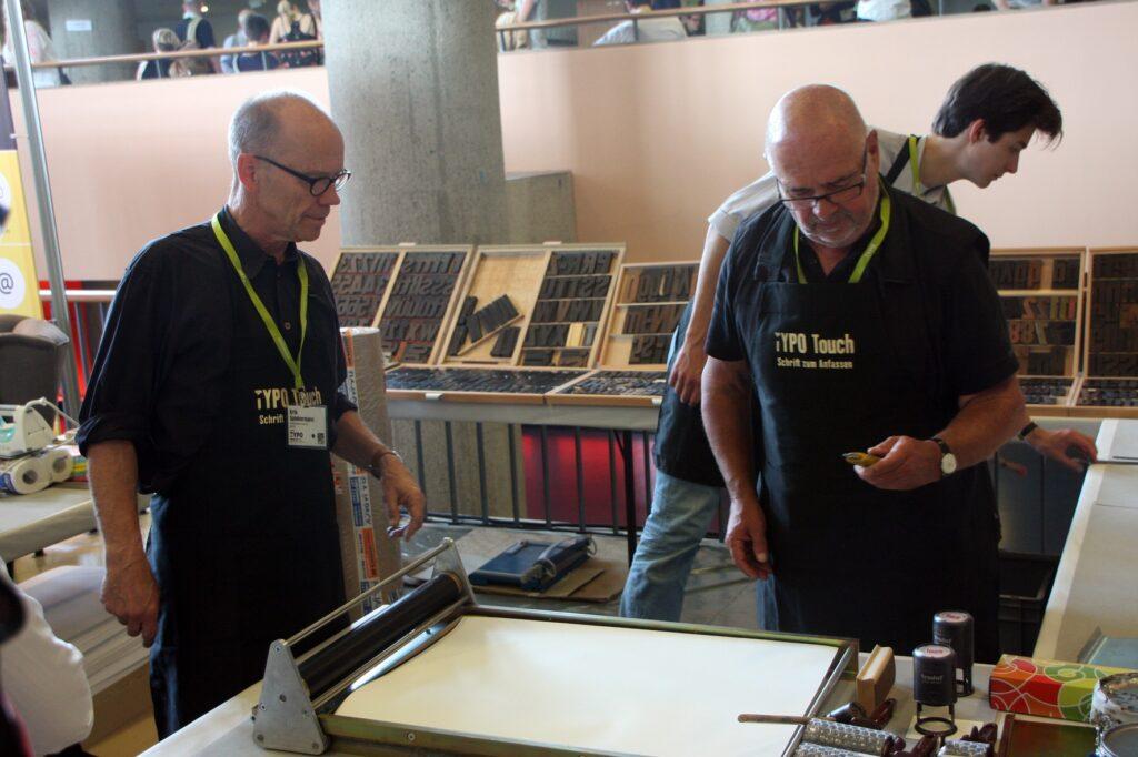 Erik Spiekermann (vľavo) viedol workshopy klasickej tlače v improvizovanej knítlačovej dielni